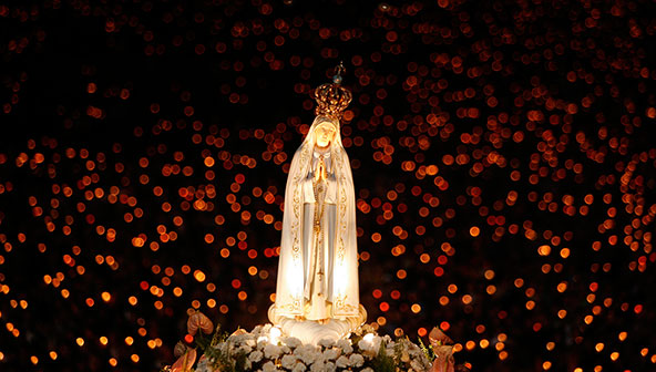 A statue of Our Lady of Fatima is carried during a candlelight vigil at the shrine in Fatima, Portugal, Oct. 12, 2007. An estimated 300,000 pilgrims converged in Fatima to celebrate the 90th anniversary of the first apparition of Mary to three shepherd children in 1917. A new, modern church was also dedicated at the shrine. (CNS photo/Nacho Doce, Reuters)