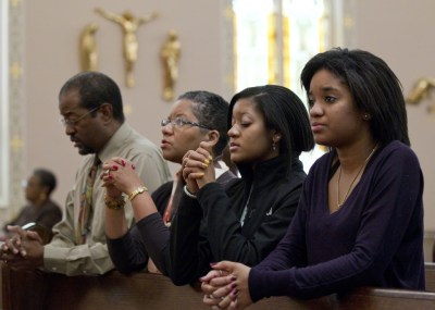 The Brooks family — Joe, Desiree, Gabrielle and Alyssa — pray after arriving for Sunday Mass at St. Joseph's Catholic Church in Alexandria, Va., in this 2011 file photo. According to the first study of its kind, Black Catholics in the U.S. are highly engaged with their religion and parish life, more so than white Catholics. (CNS photo/Nancy Phelan Wiechec)