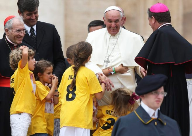 Pope Francis smiles as he meets children during his June 25 general audience in St. Peter's Square at the Vatican. (CNS photo/Alessandro Bianchi, Reuters)