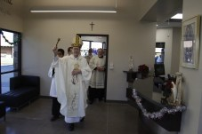 Bishop Olmsted blesses the administrative offices and break room. (Ambria Hammel/CATHOLIC SUN)