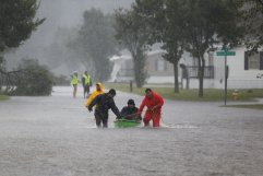 Residents help an elderly man evacuate a flooding trailer community Sept. 15 during Hurricane Florence in Lumberton, N.C. The storm continued to thrash the Carolinas with fierce winds, driving rain and catastrophic flooding. Downgraded from hurricane strength after making landfall, the storm had killed at least five people, authorities said, and trapped hundreds of others whose rescues continued as night fell Sept. 15. (CNS photo/Randall Hill, Reuters)