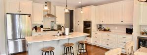 modern white kitchen design with custom cabinets, kitchen island, wood floors