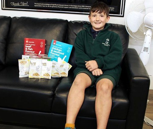 Boy sitting on a couch with cat food packets and boxes next to him