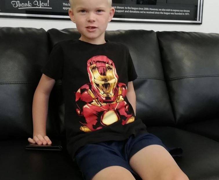 Young blonde boy sitting on a couch