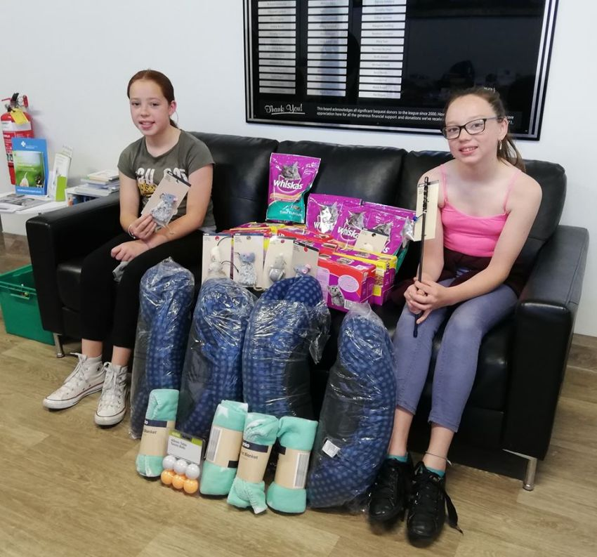 two girls sitting on a couch with many donations of cat food, beds, blankets and toys between them
