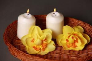 two white candles and two yellow flowers