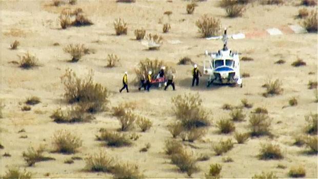 Imagem da emissora de TV NBC mostra equipe de resgate levando o segundo piloto da SpaceShipTwo, próximo ao local dos destroços