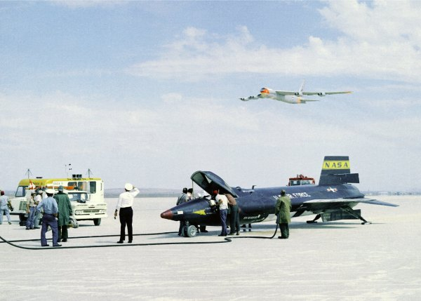 Ground personnel take care of the X-15 after flight while the NASA NB-52B mothership flights above their heads.