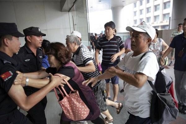 Familiares de passageiros do voo MH370 empurram policiais na entrada do prédio onde fica o escritório da Malaysia Airlines em Pequim no dia 5 de agosto de 2015; inicialmente os seguranças impediram os parentes de entrar, mas em seguida eles foram autorizados (Foto: Damir Sagolj/Reuters)