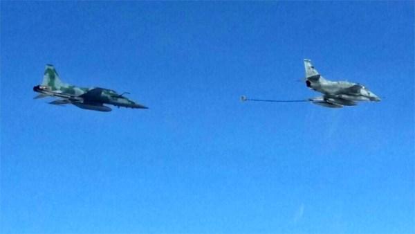 Um jato AF-1 prestes a reabastecer em voo um caça F-5EM da FAB.
