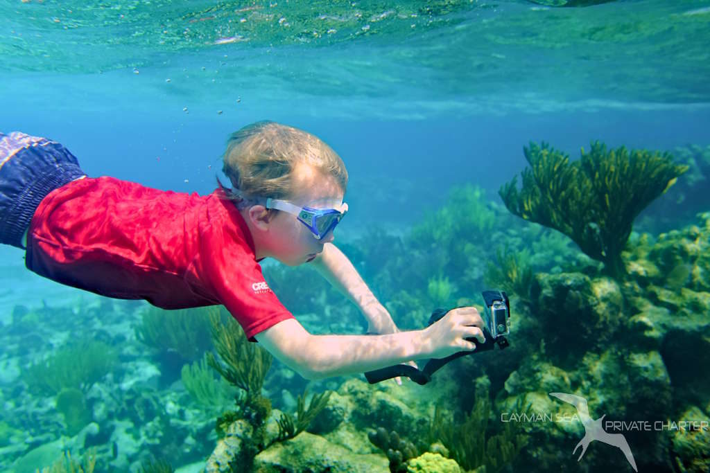 boy with camera snoreling the reef in grand cayman