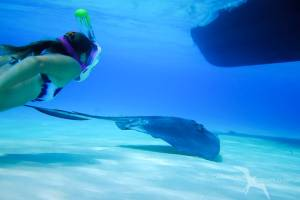 girl swimming under private charter boat at stingray city