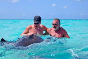 two friends laughing with a stingray on a private boat charter in grand cayman