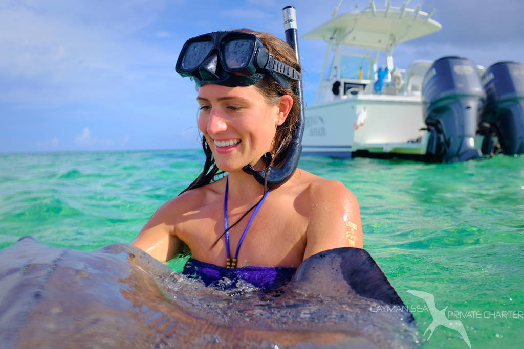 girl who didn't think should could, now holding a stingray on a private boat charter in grand cayman