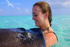 girl holding a stingray and smiling at stingray city grand cayman