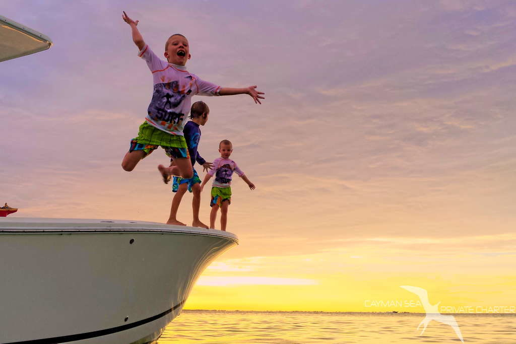 young boys jumping from charter boat on a sunset cruise in grand cayman