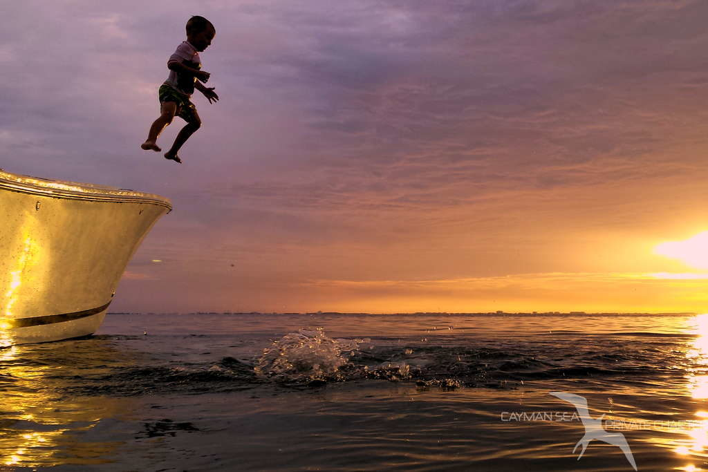 boy jumping from our charter boat with sunset behind