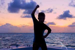 boy with sunset behind on a boat on a sunset cruise in grand cayman