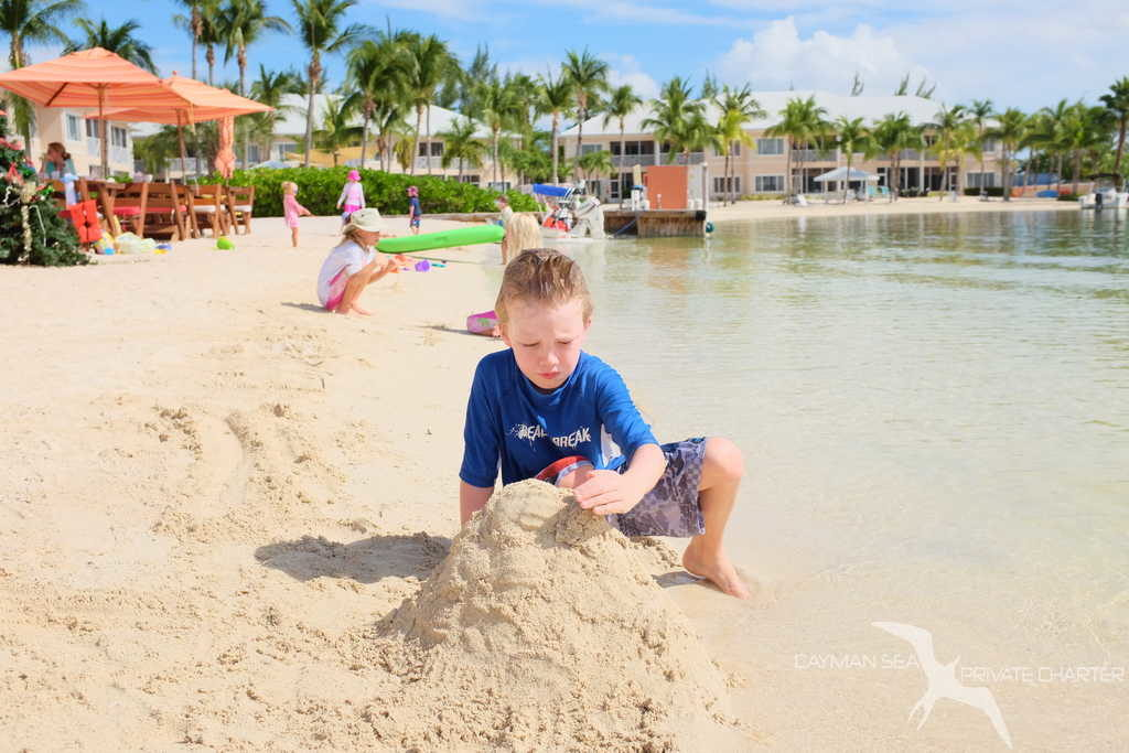 boy building a sandcastle on the beach at kaibo grand cayman on a private boat charter