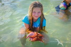 girl holding a starfish on a private boat charter to starfish point grand cayman