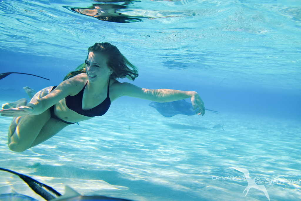 girl swimming with stingrays on a private boat charter to stingray city grand cayman