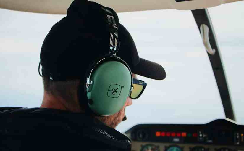 close up of a man wearing a headphone and sunglasses inside an aircraft cockpit