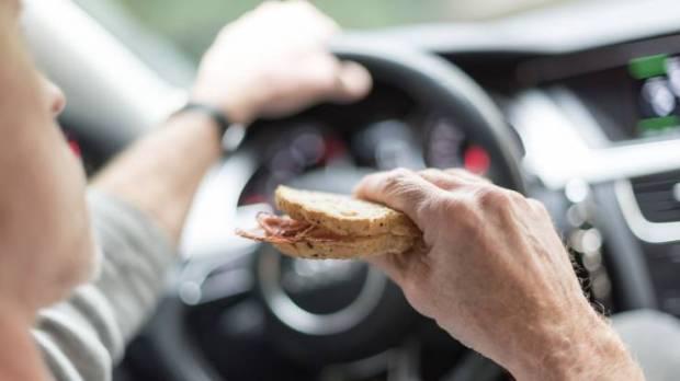 Un conducteur mange un sandwich au volant