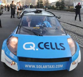 UN official Yvo de Boer, left, and Swiss schoolteacher Louis Palmer, right, arrive in a solar taxi to the United Nations' climate-change conference in Poznan, Poland, on Thursday.