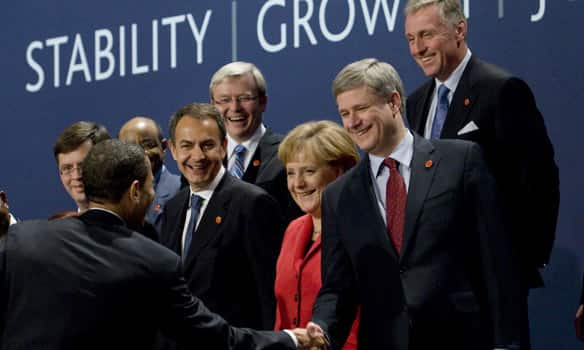 U.S. President Barack Obama shakes Prime Minister Stephen Harper's hand as G20 leaders gather to take a second family photo after the prime minister missed the first take.