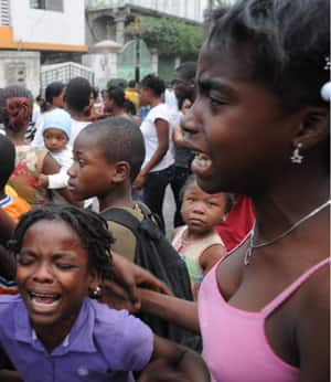 People gather in the street after an earthquake levelled many buildings and houses in Port-au-Prince Tuesday.