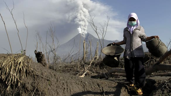 Mount Merapi volcano spews ash as a villager collects her valuables from the ruins of her house at Kali Tengah village in Sleman, near Yogyakarta, on Monday.