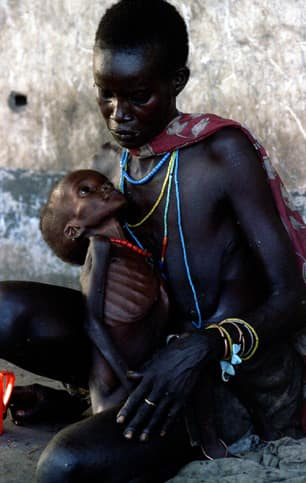 A Sudanese mother tries to feed her severely malnourished child at a feeding centre in Ayod on March 31, 1993. Thousands of Sudanese fled the civil war to Ayod.