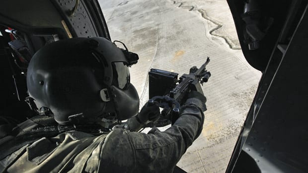 A U.S. Black Hawk helicopter door gunner scans the ground during a mission over southern Afghanistan's Kandahar province.