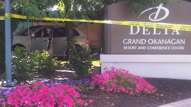 The grey Porche Cayenne SUV with doors open can be seen behind police tape outside a Kelowna hotel Sunday.