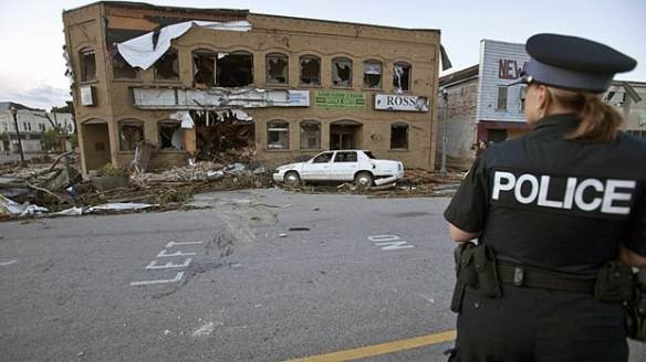 A police officer surveys tornado damage in Goderich, Ont., on Sunday. One man died, dozens were hurt and the community's downtown was devastated.