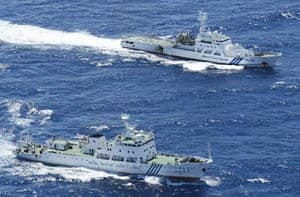 The Chinese surveillance ship Haijian No. 51, front, sails ahead of a Japan Coast Guard vessel near the disputed islands in the East China Sea on Friday.