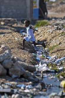 A girl jumps over an open sewage in Port-au-Prince Sept. 4, 2012. Haiti is struggling to cope with a cholera epidemic that has killed thousands and deteriorating conditions in tent camps as aid groups withdraw from the impoverished country due to a lack of funding.