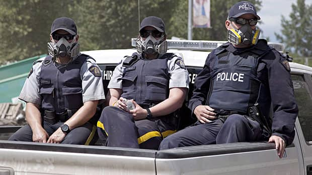 RCMP officers working in High River, Alta., on June 25, wear protective masks to prevent toxic dust from entering their lungs. The RCMP took some guns from homes they searched that they said were not stored safely and the Prime Minister's Office issued a statement Friday saying it wants them returned.