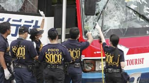 Philippine National Police investigators examine the bullet-riddled tourist bus involved in the hostage-taking in Manila.
