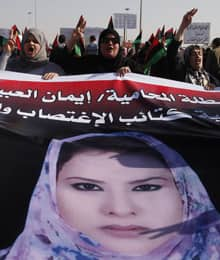 Women hold a picture of al-Obaidi during a protest in Benghazi, Libya, on March 27. Women's groups abroad have not been so quick to take up her cause.