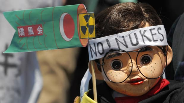 A participant holds a ventriloquial dummy wearing anti-nuclear signs at a rally protesting against the usage of nuclear energy in Tokyo on Saturday.