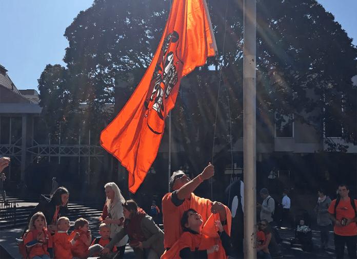 Haley and her father triumphantly raise a huge orange flag on a pole.