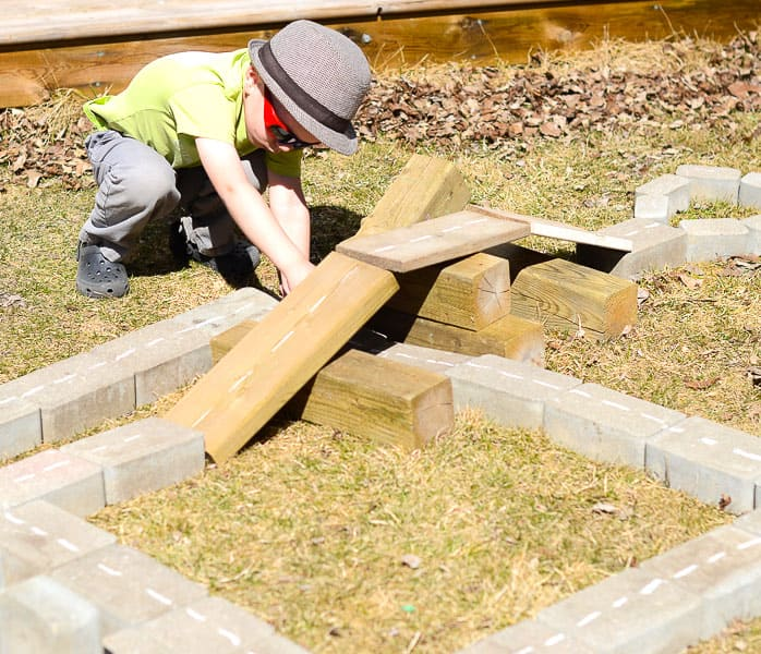 A boy working on building a city out of pieces of plywood and paving stones.
