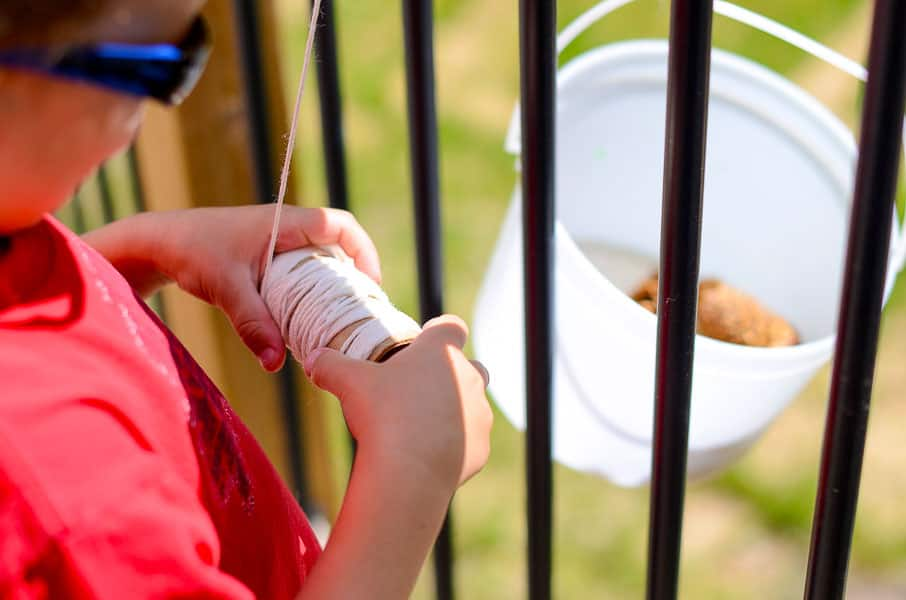 A child holding a bobbin of string which has been attached to a bucket and thrown over the edge of a deck, so that the bucket can be raised and lowered.