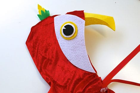 The face of the parrot glued onto the hood of the cape.