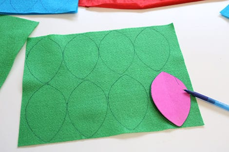 A sheet of green felt filled with 8 traced feather shapes. The shapes have been traced with pen.