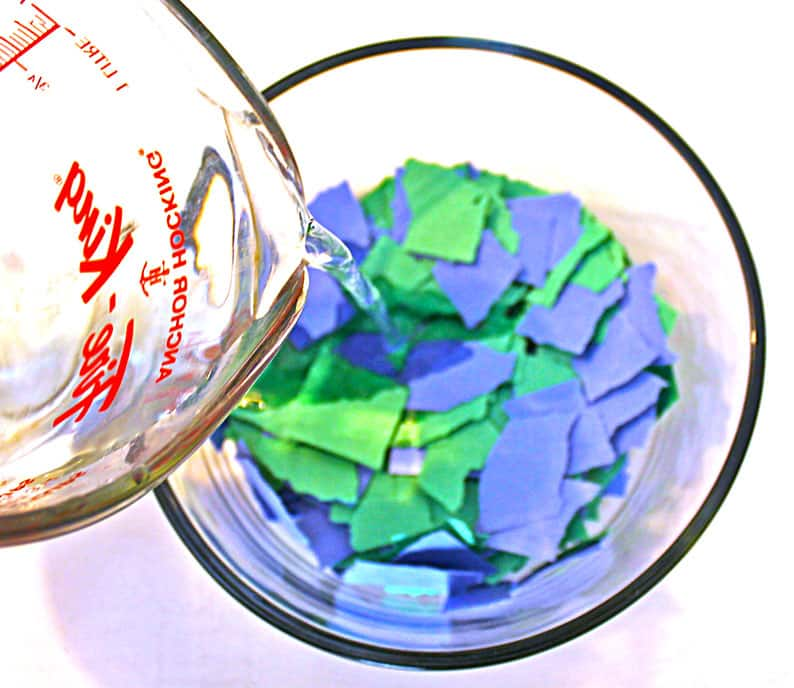 Pouring water into bowl full of torn construction paper.