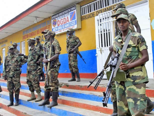 Rebels stand guard at the border entry into Rwanda