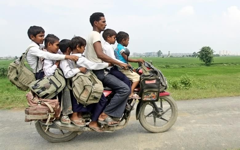 A motorcyclist carries six children on their way back home from school