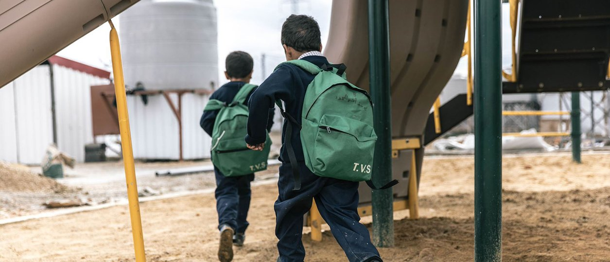 Photo of two kids with backpacks running